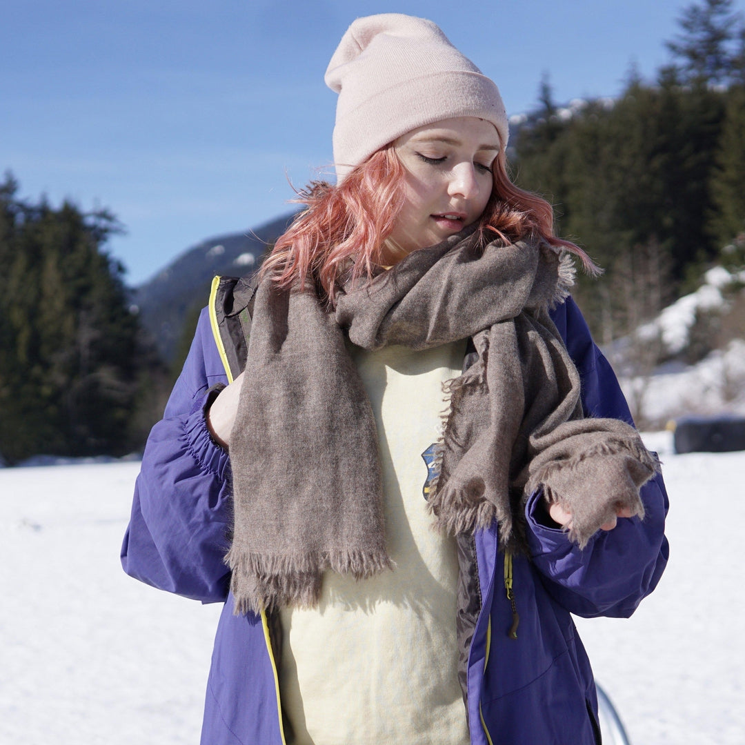 Ethical cashmere natural dye high grade cashmere scarf in dark taupe grey, worn loosely around the neck in snow