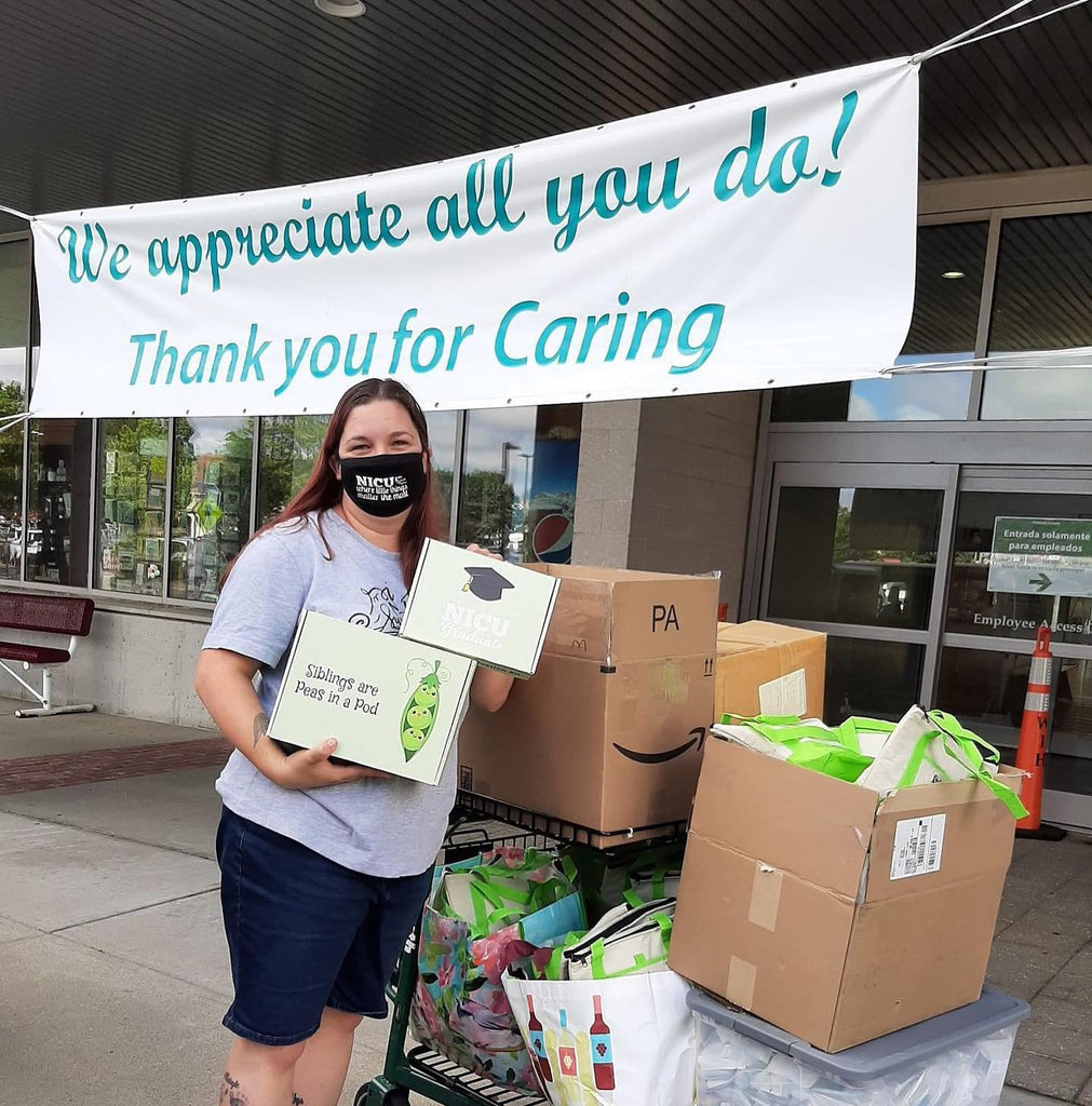 woman with mask holding green custom box outside with donation boxes