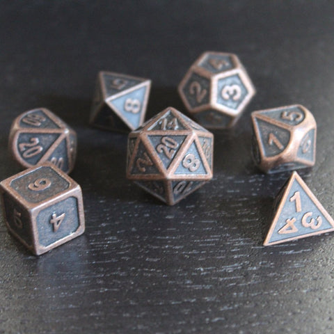 Zinc alloy cast Steampunk look with aged copper effect seven polyhedral dice lie on a dark wooden board.