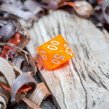 A percentile D10 luminous orange transparent plastic polyhedral dice, numbers inked with white sit on a wooden board surrounded by wood shavings.