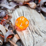 A D12 luminous orange transparent plastic polyhedral dice, numbers inked with white sit on a wooden board surrounded by wood shavings.