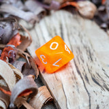A D10 luminous orange transparent plastic polyhedral dice, numbers inked with white sit on a wooden board surrounded by wood shavings.