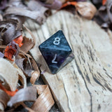 A D8 dice. Black marble with bright purple acrylic through middle with white inked numbers lie on a wooden board.