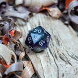 A D20 dice. Black marble with bright purple acrylic through middle with white inked numbers lie on a wooden board.