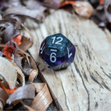 A D12 dice. Black marble with bright purple acrylic through middle with white inked numbers lie on a wooden board.