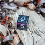 A D6 dice. Black marble with bright purple acrylic through middle with white inked numbers lie on a wooden board.