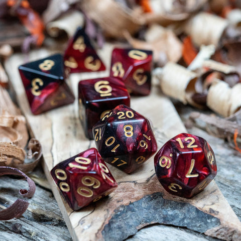 A set of polyhedral dice. Two toned black and red pearlescent finish Numbers in gold ink lie on a wooden board.
