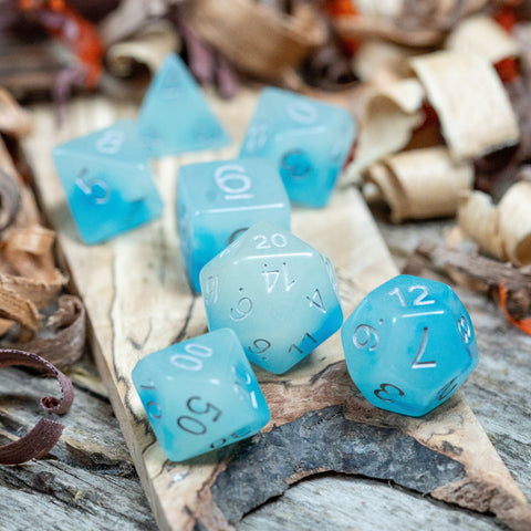 Seven Ice blue polyhedral dice lie on a wooden display. Numbers in silver ink.