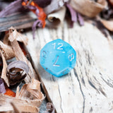 A D12 Ice blue polyhedral dice lie on a wooden background. Numbers in silver ink.