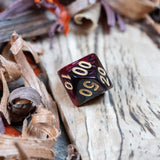 A percentile D10 dice. Two toned black and red pearlescent finish Numbers in gold ink lie on a wooden board.