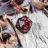 A D20 dice. Two toned black and red pearlescent finish Numbers in gold ink lie on a wooden board.