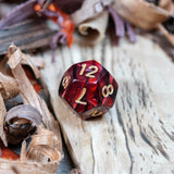 A D12 dice. Two toned black and red pearlescent finish Numbers in gold ink lie on a wooden board.