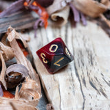 A D10 dice. Two toned black and red pearlescent finish Numbers in gold ink lie on a wooden board.