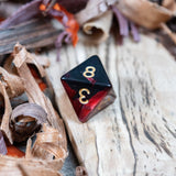 A D8 dice. Two toned black and red pearlescent finish Numbers in gold ink lie on a wooden board.