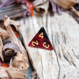 A D4 dice. Two toned black and red pearlescent finish Numbers in gold ink lie on a wooden board.