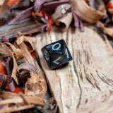 A D10 dice. Black marble with sapphire blue acrylic through middle,