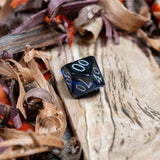 A D10 percentile dice. Black marble with sapphire blue acrylic through middle,