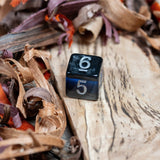 A D6 dice. Black marble with sapphire blue acrylic through middle,