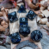 A set of  polyhedral dice. Black marble with sapphire blue acrylic through middle. Numbers inked with white, lie on a wooden board.