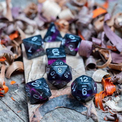 A set of  polyhedral dice. Black marble with bright purple acrylic through middle with white inked numbers lie on a wooden board.
