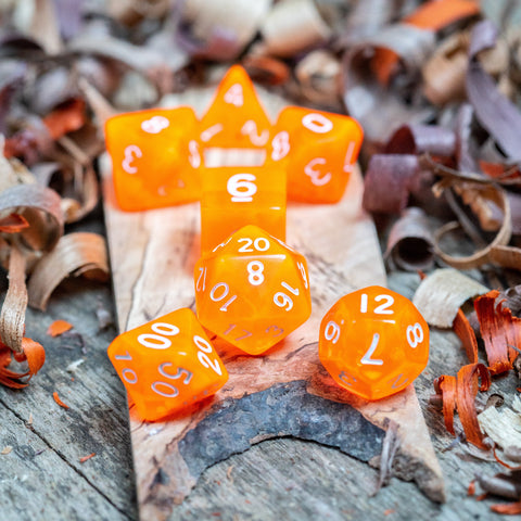 Seven luminous orange transparent plastic polyhedral dice, numbers inked with white sit on a wooden board surrounded by wood shavings.