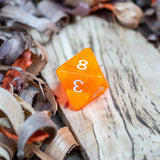 A D8 luminous orange transparent plastic polyhedral dice, numbers inked with white sit on a wooden board surrounded by wood shavings.