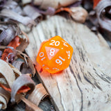 A D20 luminous orange transparent plastic polyhedral dice, numbers inked with white sit on a wooden board surrounded by wood shavings.