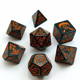 A set of seven polyhedral dice placed in an arrow on a white background. Black acrylic Filigree designs around numbers. The D6 has Halloween symbols in orange. Numbered with orange ink.