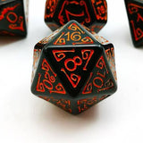 Black acrylic D20 dice with bright orange filigree designs around numbers, blurred similar dice behind sits on a white background.