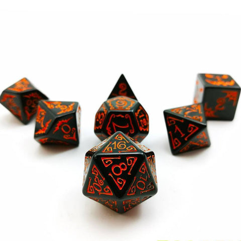 A set of seven polyhedral dice placed in an arrow on a white background. Black acrylic Filigree designs around numbers. Numbered with orange ink.