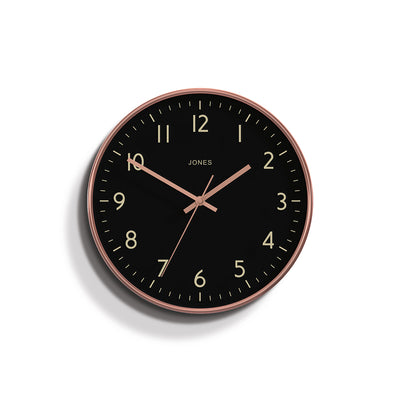 Studio wall clock in a copper effect by Jones Clocks with a reverse black Arabic dial and straight metal hands