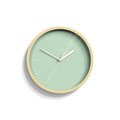 Small scandi Spin wall clock by Jones Clocks in a pale plywood effect with a green marker dial