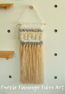 Woven wall hanging in shades of white