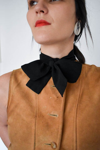 A unisex vintage black silk bowtie and light brown leather vest