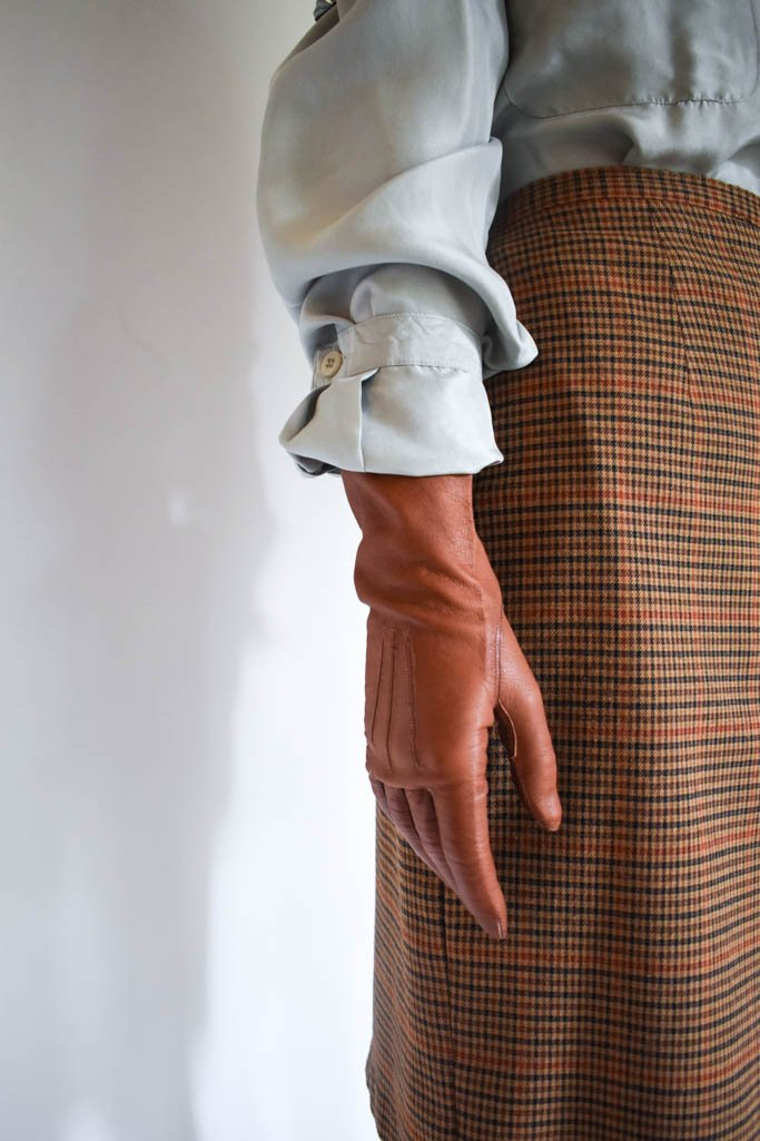 A pair of womens small vintage brown leather gloves with a seafoam silk button down