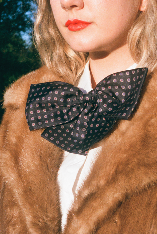 A unisex vintage navy bowtie pin and brown fur coat