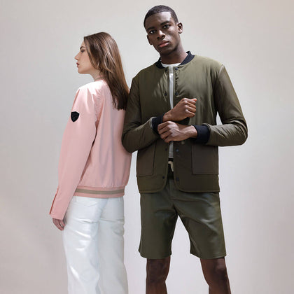 Man wearing steel grey-coloured thigh-length down parka with hood, standing behind a woman wearing a steel grey-coloured knee-length parka with hood.