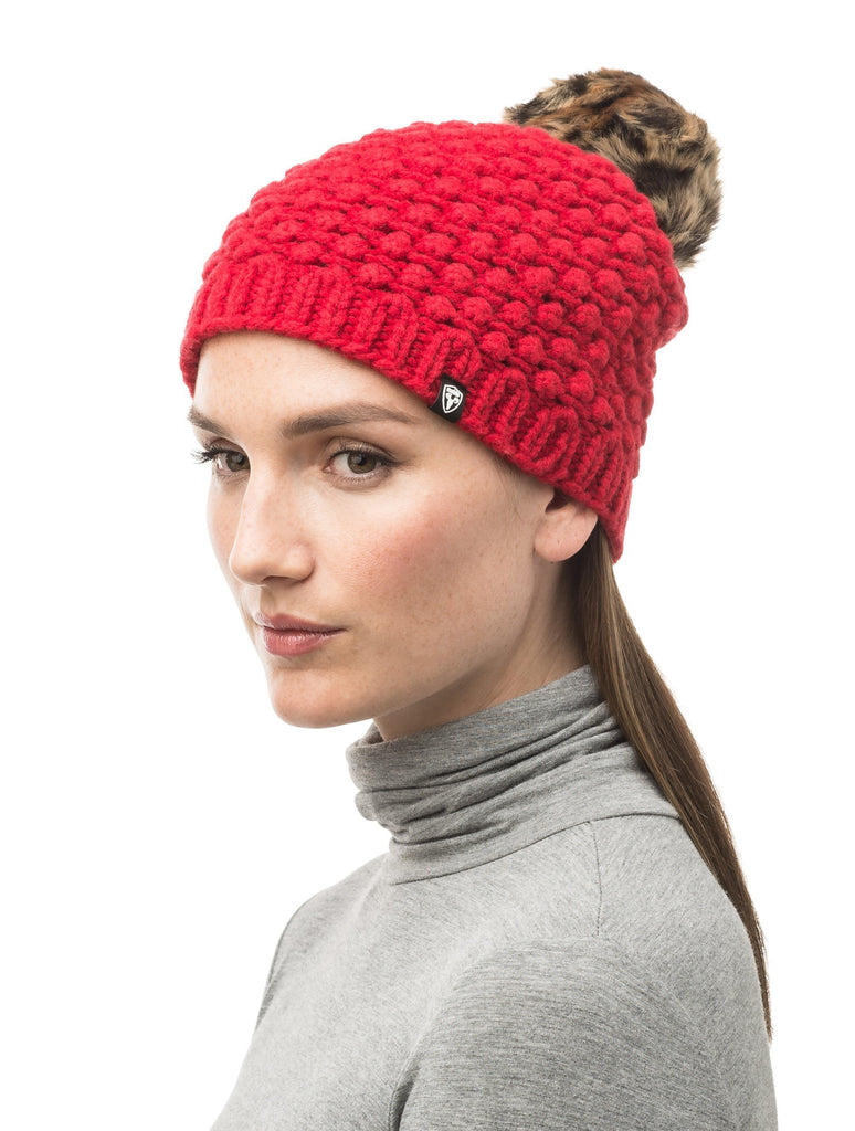 Red bulk knit toque with faux fur pom pom on top.