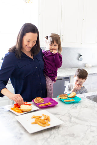 mom making meal for two children