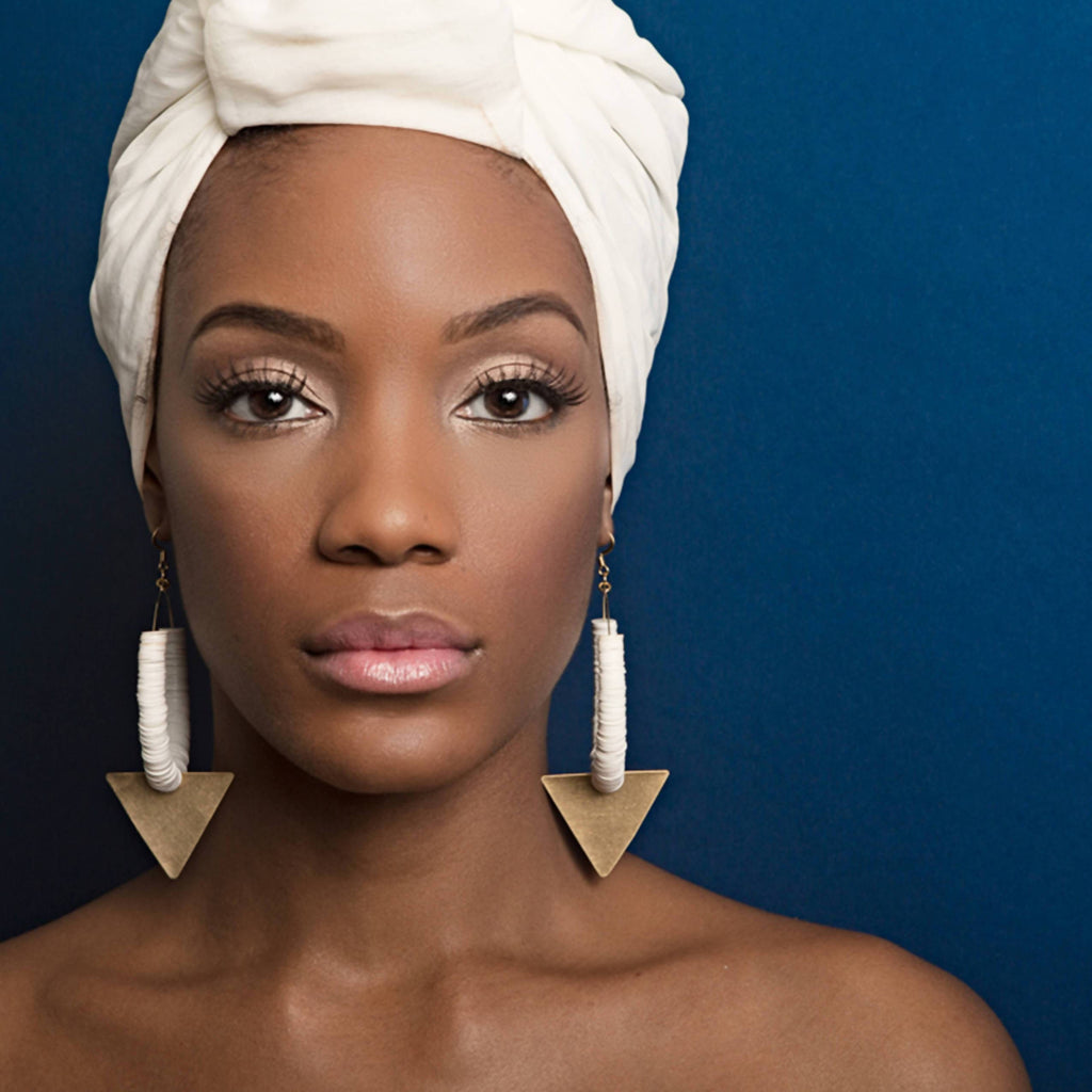 Model wearing African hoop earrings made of vinyl disc beads with brass triangle pendant, gold-filled ear wire.