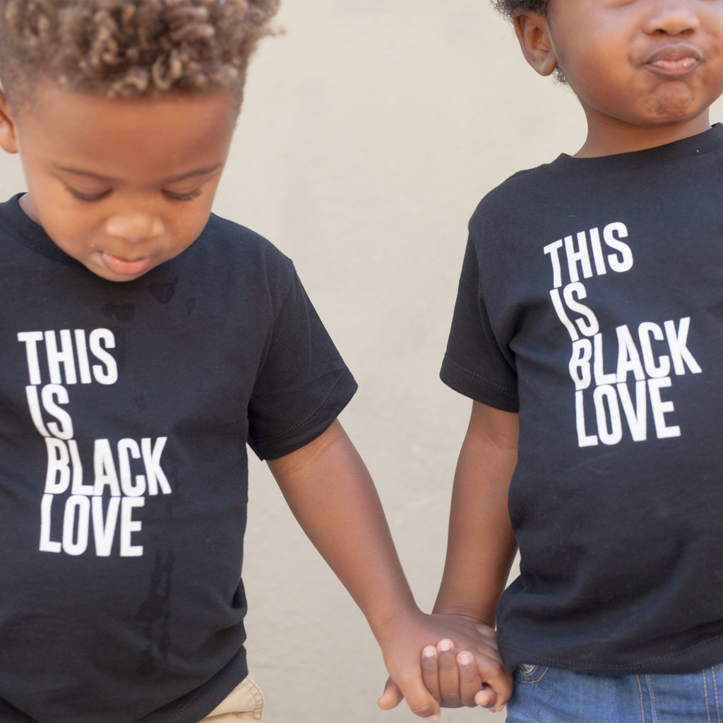 "Two children wearing ""This Is Black Love"" short sleeve onesie. 100% Cotton unisex design for toddlers."