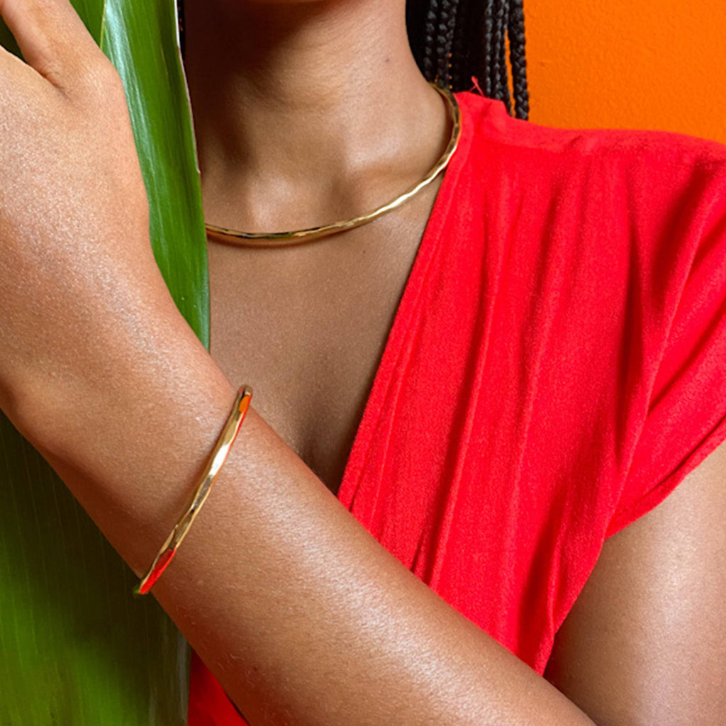 Model wearing minimal hammered brass choker necklace with matching bangle.
