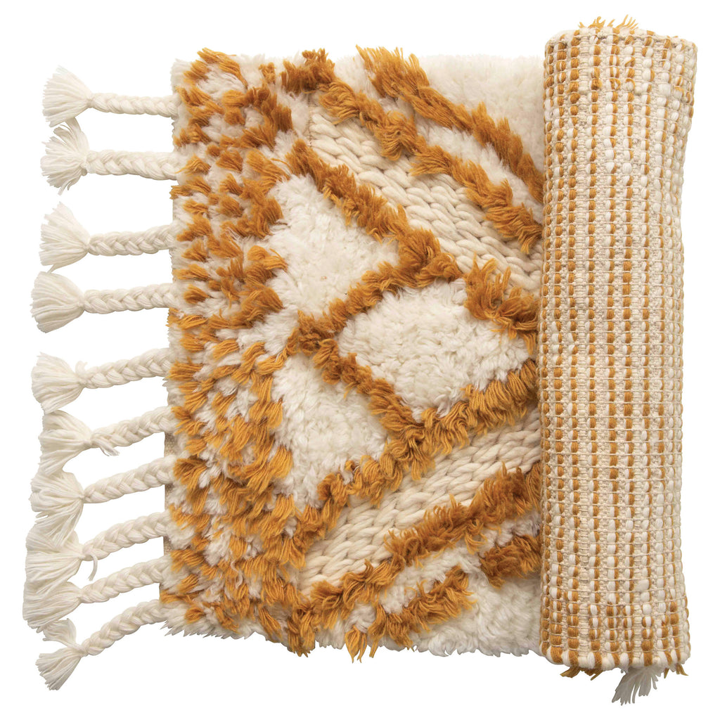 Wool tufted patterned rug with braided tassels, natural and brown mustard color.