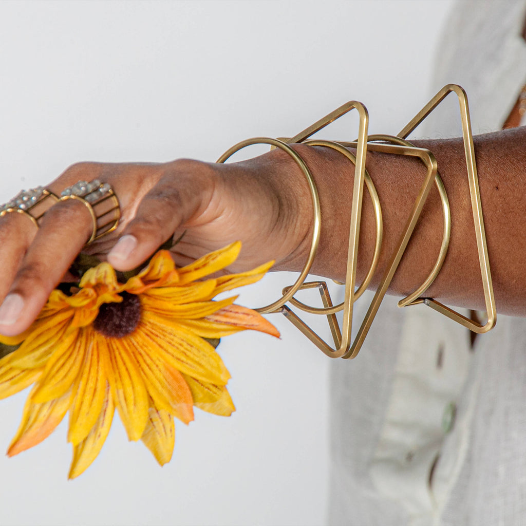 Woman wearing unique solid brass abstract cuffs and flower