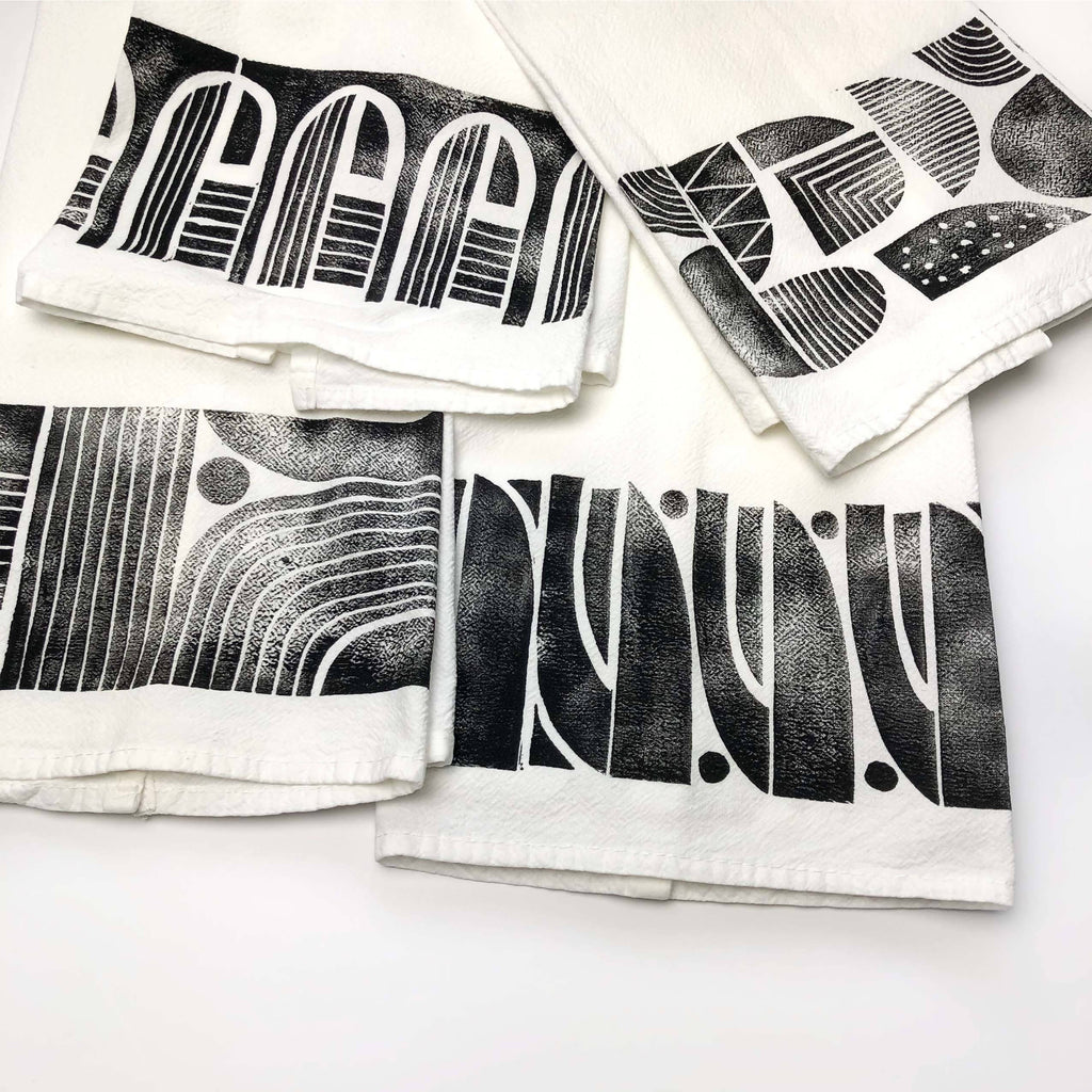Handprinted set of 4 kitchen towels, each with a different modern pattern.