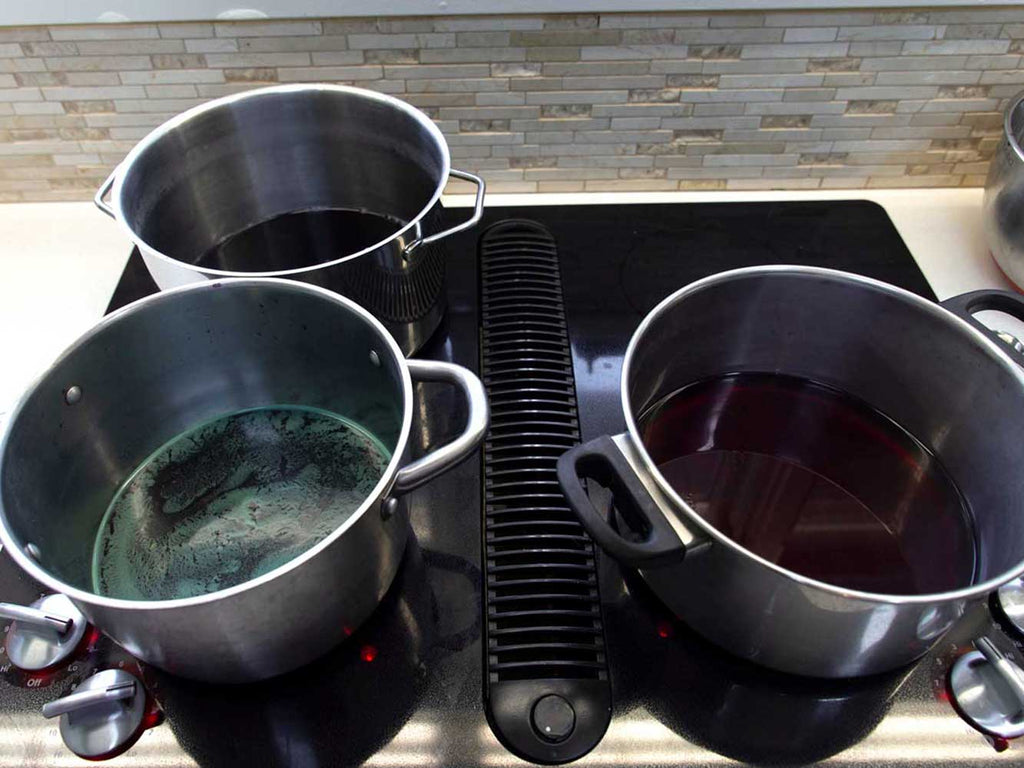 Three stainless steel pots on a black stovetop. Each pot contains red cabbage dye water.