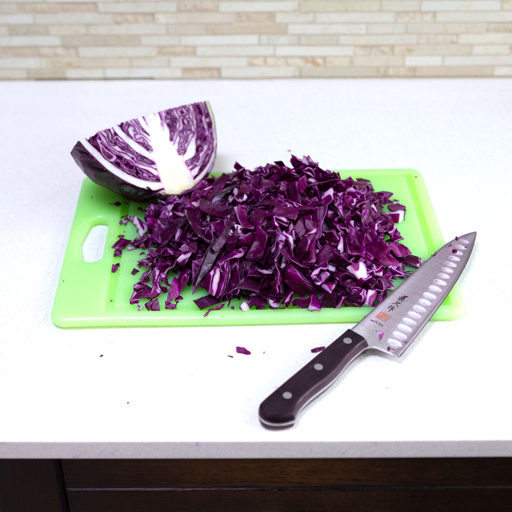 Half a head of chopped red cabbage on a cutting board. A knife is laying on right side of the board.