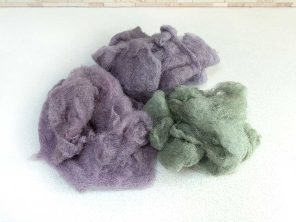 Three piles of fluffy carded wool on a white countertop. One pile is green, one pile is grey-purple, one pile is pink-purple.
