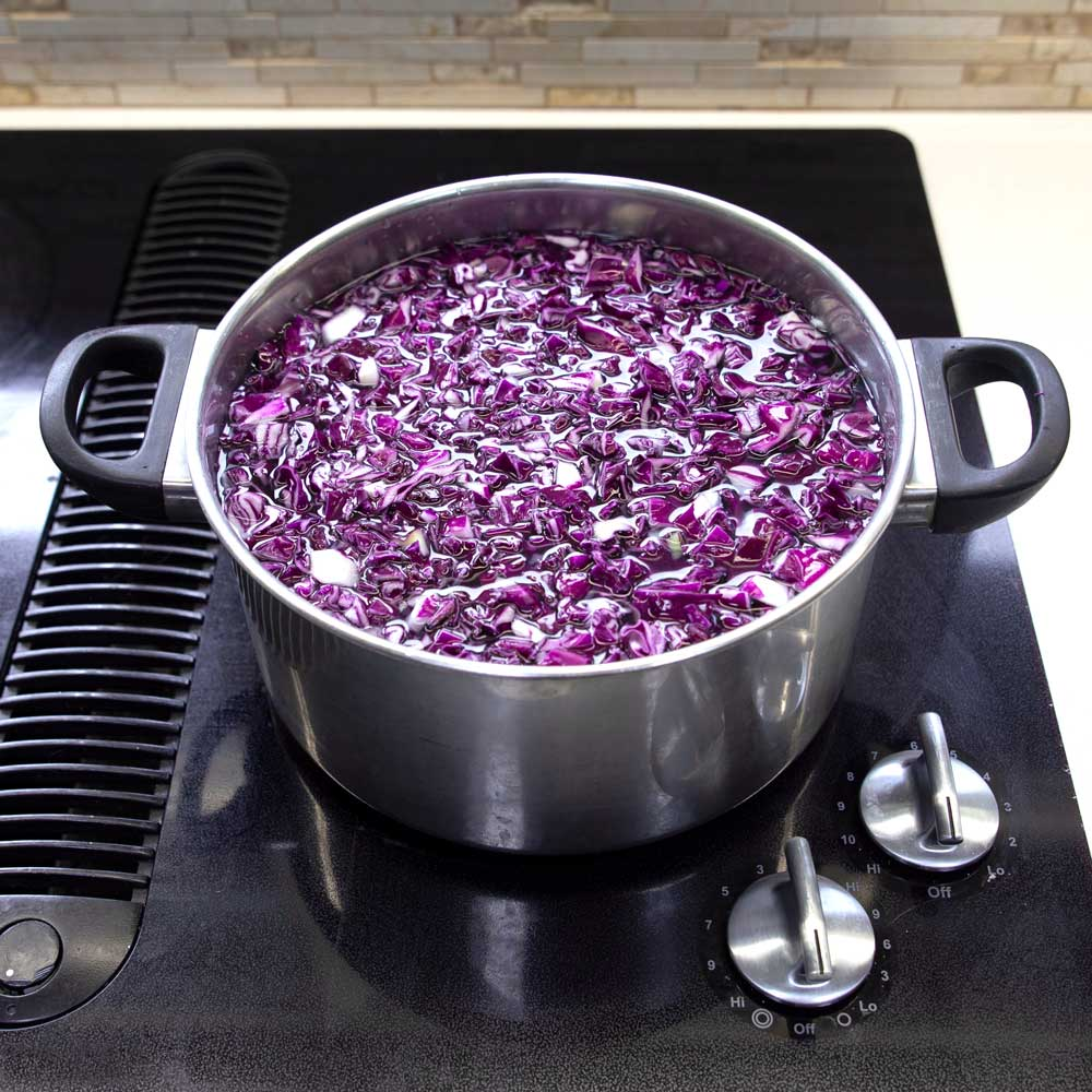 A stainless steel pot filled with chopped red cabbage and water sitting on a stovetop.