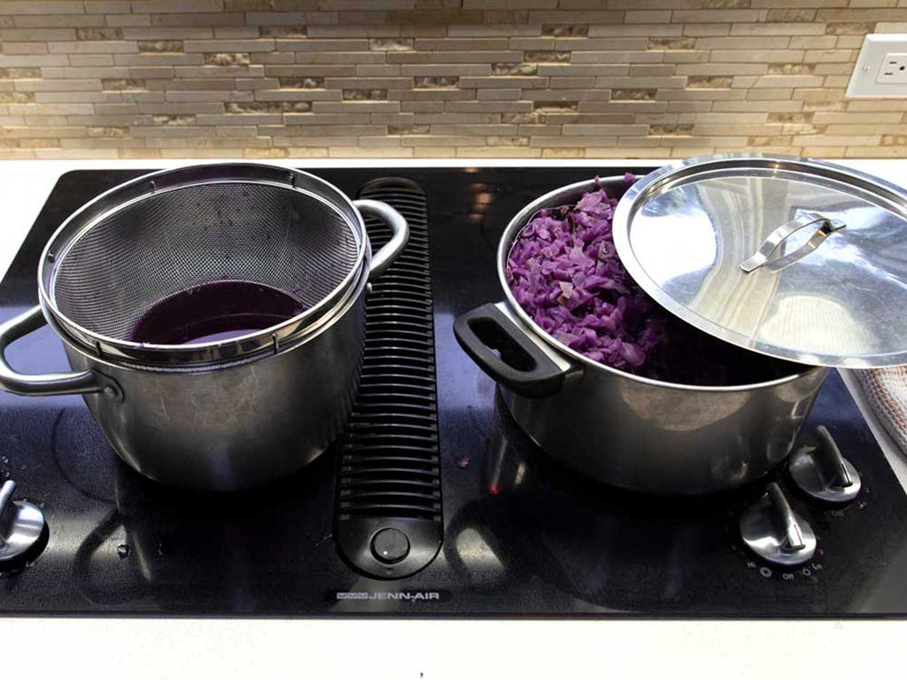 two stainless steel pots sitting on a stovetop. Inside the left pot is a strainer filled with purple water. Inside the right pot is chopped red cabbage that has had the water strained from it.